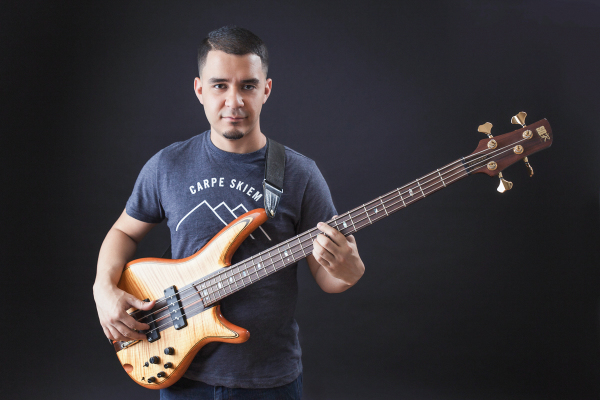 indoor headshot man holding orange bass musician bassist playing